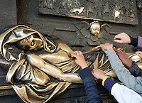People touching a .statue of local hero Everard t'Sceclaes, stroking the statue brings good luck. Grand Place, Brussels, Belgium