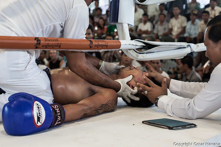 SIEM REAP, CAMBODIA. Doctors and referees check for vital signs on one of the fighters after he was knocked out by his opponent during a fight in the Siem Reap arena in Cambodia. Pradal Serey or Kun Khmer -free fighting- is an unarmed martial art from Cambodia. Compared to other forms of Southeast Asian kickboxing, Kun Khmer emphasises more elusive and shifty fighting stances. The Cambodian style tends to utilise more elbows than that of other regions. Evidence shows that a style resembling pradal serey existed in the 9th century, leading the Khmer to believe all Southeast Asian forms of kickboxing started with the early Mon-Khmer people. They maintain that Pradal Serey has influenced much of the basis of Muay Thai. During the Khmer Rouge genocide, traditional martial arts were banned and many boxers were executed or worked to death, which nearly caused the death of pradal serey. Nowadays, Kun Khmer is making a strong comeback in Cambodia, with fighters attempting to market their style of boxing at the same caliber of Muay Thai. Photography: ©Omar Havana