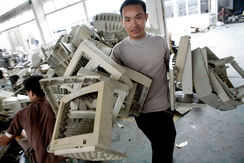 A migrant worker processes plastic computer screen casings in a workshop specialising in recycling electronic trash in Panyu, China. Each year, between 20 and 50 million tons of electronic waste is generated globally. Most of it winds up in the developing world. Some of the most popular destinations for dumping computer hardware include China, India, and Nigeria. It can be 10 times cheaper for a ìrecyclerî to ship waste to China than to dispose of it properly at home. With the market for e-waste expected to top $11 billion by 2009, itís lucrative to dump on the developing world.