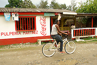 Garifuna woman riding a bicycle  in the Garifuna village of Triunfo de la Cruz, Honduras....