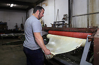 Still wet and immediately after cleaning process, the skin goes through a mechanical press which remove the last fur at the tannery factory of Scriptorium SL in Valencia, Spain. Picture by Manuel Cohen