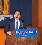 Elmont, New York, USA. April 5, 2016. Assemblyman TODD KAMINSKY, the Democratic party's candidate in the upcoming special election for the State Senate seat, is about to introduce former President Bill Clinton at an Organizing Event in Elmont, Long Island, on behalf of his wife, Hillary Clinton, the leading Democratic presidential candidate. Podium has 'Fighting for us' slogan on sign.The the Special Election for NYS Senate Seat and the New York Presidential Primary both take place April 19th.