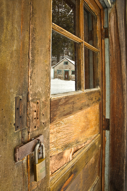 The Dahl Saloon reflects in the front door of the Kelley's Saloon at the Garnet Ghost Town in Montana, USA