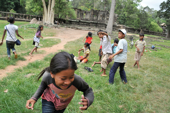Children play on Angkor Wat site in Siem Reap, Cambodia. Many children are out of school due to poverty.
