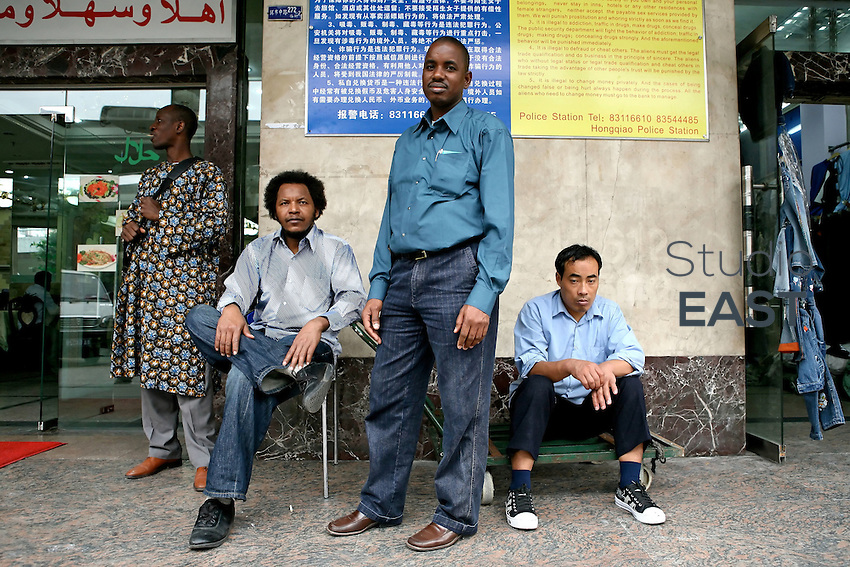"""Africans and Chinese in front of Tianxiu building, housing African businesses, in Xiaobei Street, the """"African street"""" of Guangzhou, China, on March 16, 2007. Chinese goods flow to Africa, but men flow the other way: thousands of Africans are now settling in China. China's Southern metropolis Guangzhou has the country's largest African population, now exceeding 7,000. Photo by Patrick Wack/Pictobank"""