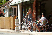 Zoe talking to Sam outside cafe, holding white Charge Decanter bicycle .   Sunninghill, Berks.    July   2013.      pic copyright Steve Behr / Stockfile