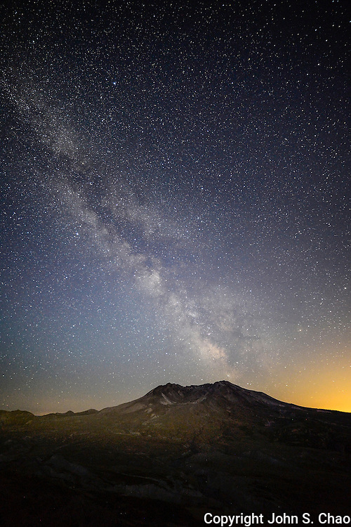 Milky Way passes over a light-painted Mount St. Helens, Washington State. Light pollution likely from Vancouver, WA in lower right frame.
