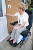 Female wheelchair user unlocking the front door to her home,