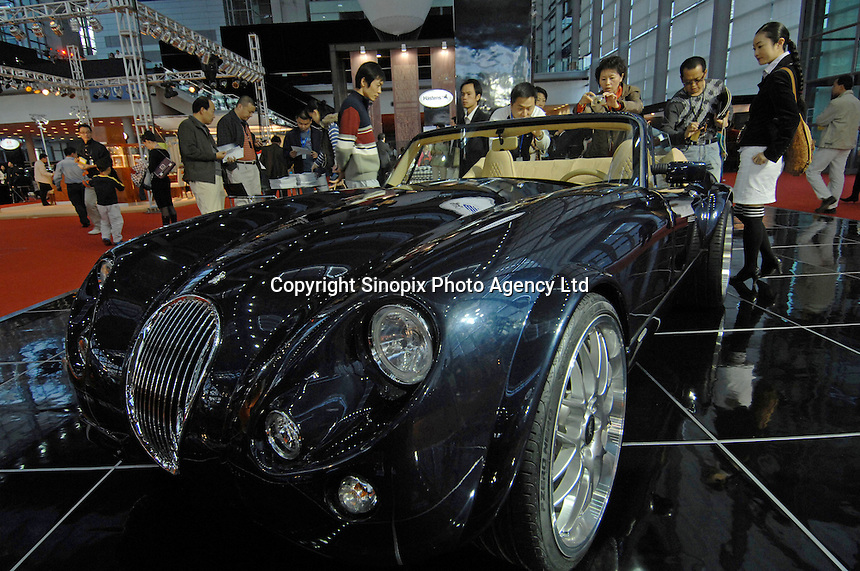"Guests look at the German made Wiesmann MF3 roadster sports car at the ""Top Show"" luxury goods fair in Shenzhen, China. The car is a limited edition and retails for 3 million rnb (approx - 200,000 sterling). The German specialty-car has a show-room in Beijing and Shanghai."