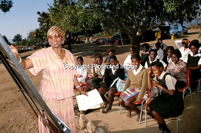 EDPRIMA19114.Education. School. Primary. Mutale. Tshandama Primary School. Ernistene Wilson, 58 years old. Peace corps volunteer. Teaching an outdoor class. She completed a Doctorate in African-American teachers., '97. Class, students, school uniform..©Per-Anders Pettersson/iAfrika Photos.