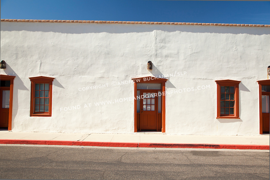 Colorful red doors and windows stand out on a white stucco building in Tucson, AZ