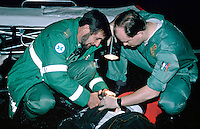 Paramedics attend a victim of a road traffic accident. They are cutting the casualty clothes to check for any signs of injuries. This image may only be used to portray the subject in a positive manner..©shoutpictures.com..john@shoutpictures.com
