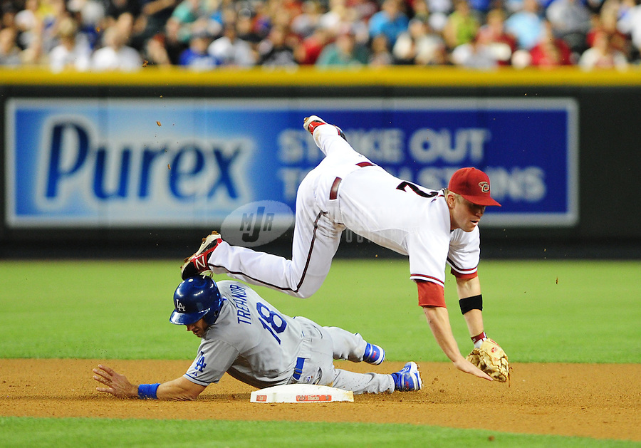 May 21, 2012; Phoenix, AZ, USA; Arizona Diamondbacks second baseman Aaron Hill flies above Los Angeles Dodgers base runner (18) Matt Treanor after forcing him out in the fourth inning at Chase Field.  Mandatory Credit: Mark J. Rebilas-