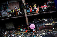 People outside their homes and on a street in the slum district of Tondo.