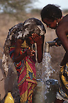 Somali girl washing and  filling water  a can from a borehole, Wajir, Somaliland, Kenya