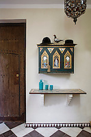 A painted cabinet creates a colourful feature on the pale wall of the entrance hall