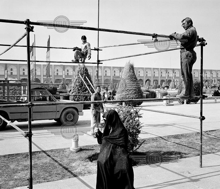 A woman in a black chador walks past a group of men errecting scaffolding in Maidan Naqsh-e Jahan (Iman Square).