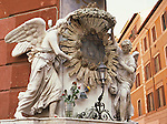 Angels on religious shrine, corner of building in Rome, Italy