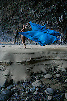 A young woman holds a blue cloth in the wind under the archway at sandy Honopu Beach, Na Pali Coast, Kaua'i.