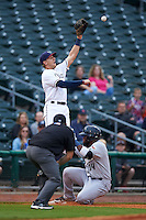 NW Arkansas third baseman Hunter Dozier (9) jumps for a throw as Yeison Asencio (14) slides into third during a game against the San Antonio Missions on May 30, 2015 at Arvest Ballpark in Springdale, Arkansas.  San Antonio defeated NW Arkansas 5-1.  (Mike Janes/Four Seam Images)