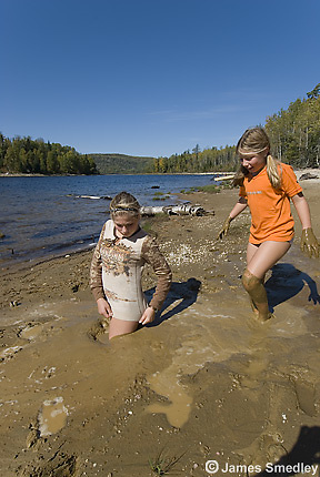 Young girls getting stuck in the mud on a beach