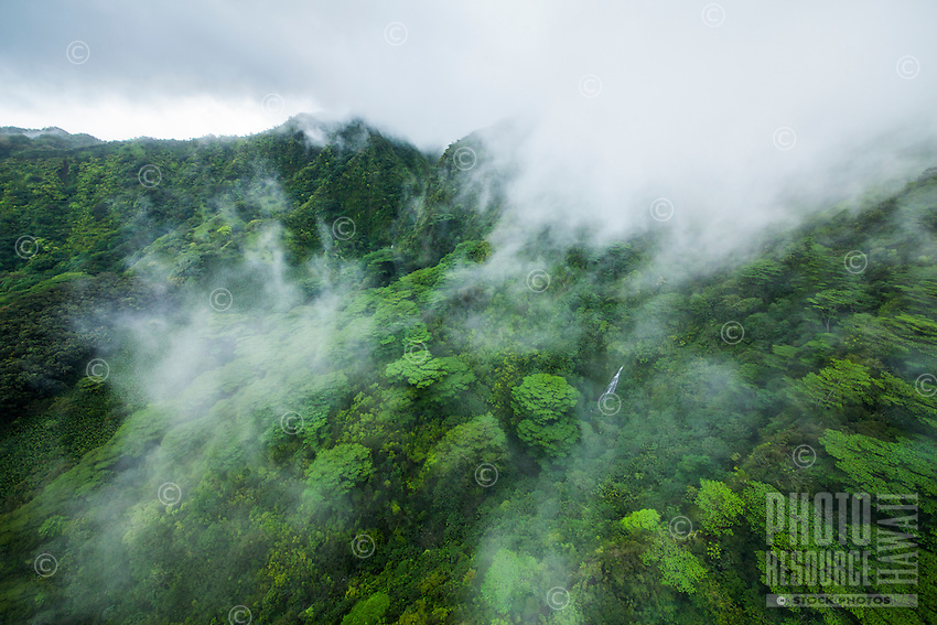 An aerial view of a waterfall through cloud cover over Manoa Valley, O'ahu.