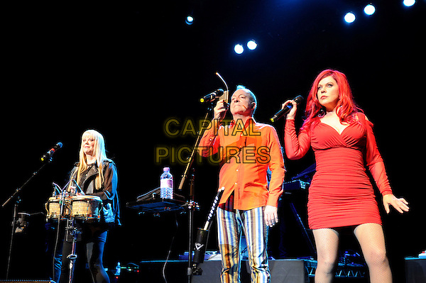 Cindy Wilson, Fred Schneider &amp; Katie Pierson<br /> The B 52's performing in concert, Indigo2, Greenwich, London, England. 16th August 2013<br /> on stage in concert live gig performance performing music half length black leather jacket drums orange shirt blue white stripe trousers red dress singing <br /> CAP/MAR<br /> &copy; Martin Harris/Capital Pictures