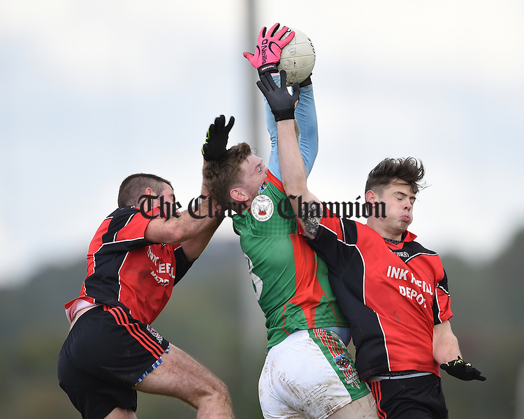 Keith Sexton of Kilmurry Ibrickane  in action against Sean O Connor and Colin Ryan of Meelick during their Junior A  county final at Gurteen. Photograph by John Kelly.