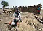 Children stand in front of the wall of a burned hut in Leu, a village in the contested Abyei region along the border between Sudan and South Sudan. The village was looted and burned in 2011 when soldiers and militias from the northern Republic of Sudan swept through the area, chasing out more than 100,000 Dinka Ngok residents. A few thousand families have returned to the region since northern combatants withdrew in 2012, yet their life is precarious. In Leu, the Catholic Church rehabilitated a clinic and drilled a well. For political and logistical reasons, the Catholic Church is one of the few organizations willing to openly accompany the people of Abyei during these uncertain times.