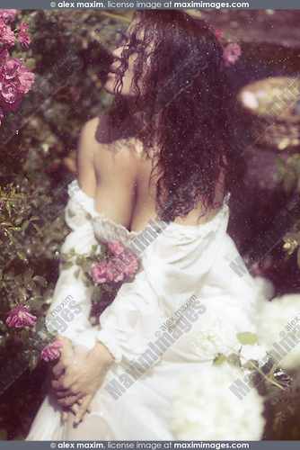 Sensual portrait of a beautiful sexy romantic woman with long wet dark hair and wet summer dress sitting in the rain in a rose garden
