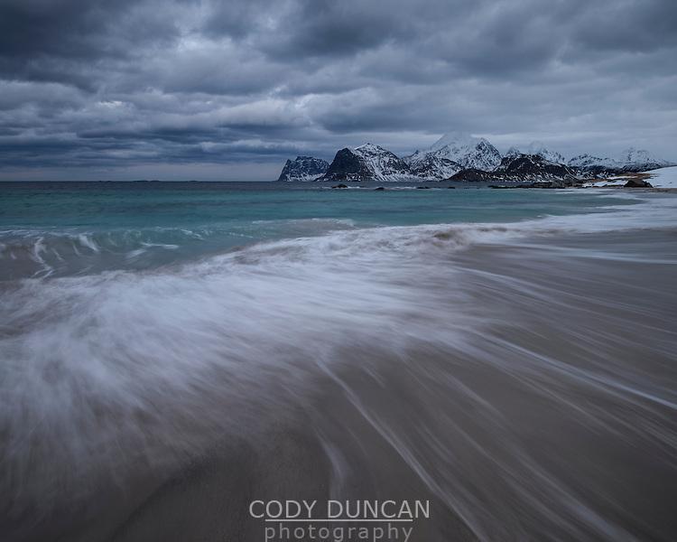 Wave washes over Storsandnes beach, Flakstadøy, Lofoten Islands, Norway