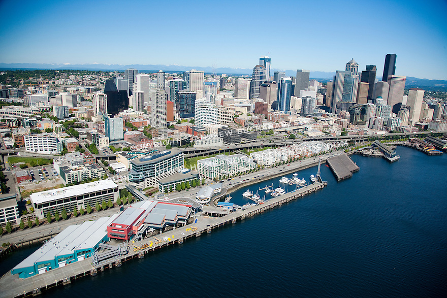 An aerial view of the downtown Seattle waterfront skyline and northern portions of the Alaskan Way viaduct / Highway 99 at the Bell Harbor Marina and cruise ship terminal on a sunny summer day.