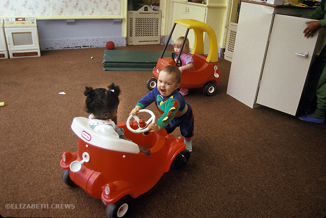 Berkeley CA Exuberant baby playing with car toy at day care, others less excited