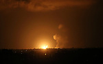 A picture taken on July 20, 2018 shows explosions during an Israeli air strike in Khan Yunis in the southern Gaza Strip. Photo by Ashraf Amra