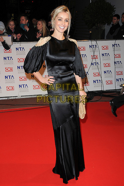 LOUISE REDKNAPP.The 15th National Television Awards held at the O2 Arena, London, England..January 20th, 2010.NTA NTAs full length maxi dress black silk satin gold clutch bag epaulettes shoulders beige hand on hip.CAP/CAS.©Bob Cass/Capital Pictures.