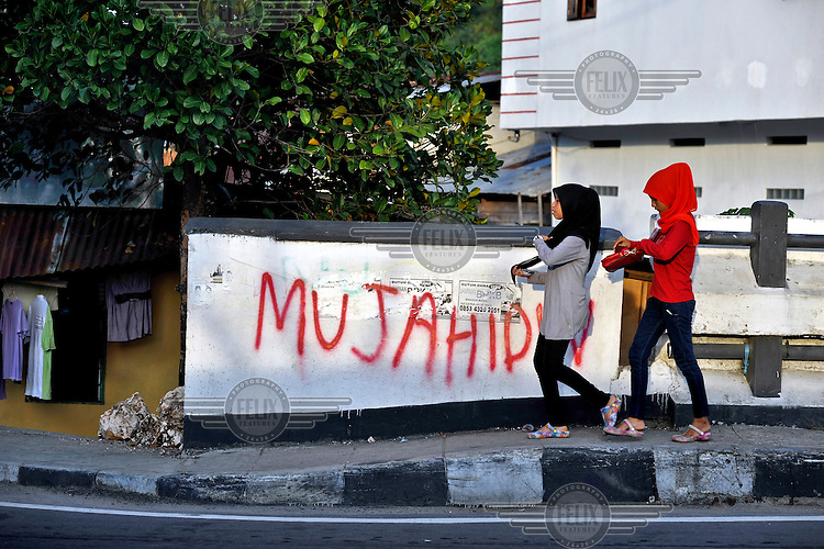 """Graffiti reading """"Mujahidin"""" - Muslim Holy Warriors - in a majority Muslim area within overwhelmingly Christian Ambon City. The 1999-2002 religious war between Maluku's Christian and Muslim populations, mainly centred on Ambon Island, led to over 5000 deaths and to around 500,000 people become displaced. Destroyed homes and offices, churches and mosques are slowly being either torn-down or renovated.  Urban centres, such as Ambon City, continue to be split along largely sectarian lines, and tensions are never far below the surface. Riots between Christian and Muslim youths erupted in September 2011 and, most recently, June 2012, though luckily simmered down just as quickly, partly due to community leaders learning how to defuse tensions from the earlier, more devastating, conflagration. /Felix Features"""