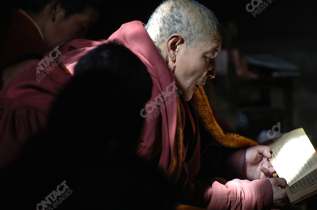 A ray of sunlight illuminated a nun and her text during a session of chanting at the Tidron Nunnery in central Tibet. November 15, 2006