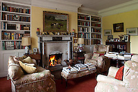 A cosy sitting roomis furnished with well-used chintz-covered armchairs and filled with piles of books and family memorabilia