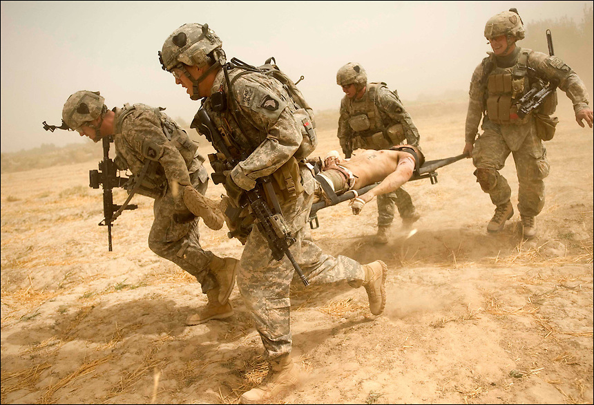 U.S. soldiers from Task Force Strike, near FOB Fitzpatrick, Zhari, Afghanistan, carry a U.S. soldier who was wounded on patrol by an IED, September 19th, 2010. Coalition forces have been making a big push south to engage this Taliban stronghold near the city.