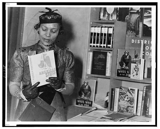 "Author and WPA fieldworker Zora Neale Hurston looks at ""American Stuff,"" an anthology of prose and verse by members of the Federal.Writers' Project, at the New York Times Book Fair in 1937. Library of Congress Prints and Photographs Division."