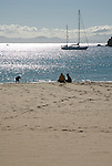 Couple and their dog sitting on beach close to the shore, with a sailing yacht at anchor and the Straits of Gibraltar and the coast of Morocco in the background.