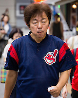 "A Cleveland Indians ""fan"". He can be a real fan. Or he could bought this t-shirt in a bargain shop. There are many shops in Japan that sell goods with American stores and teams logos. ""Whole Foods"", for example, is popular in Harajuku."