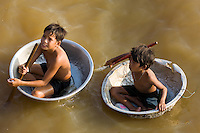 Domestic tin basins have been turned into make-shift boats by these boys so that they can get around their floating village on Tonle Sap Lake in Cambodia. They can not always do this since Tonle Sap Lake swells to cover ten thousand square kilometres at the end of the rainy season and tropical storms can blow up quickly.