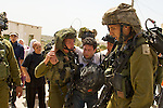 IDF soldiers arrest an injured peace activist after entering the village of An Nabi Salih near Ramallah on 11/06/2010. The injured man had tried to prevent a fight between the soldiers & two Palestinian women & was knocked to the ground by a soldier who subsequently kicked him as he lay injured.