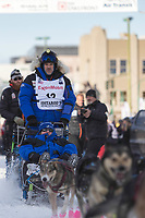 Jason Campeau and team leave the ceremonial start line with an Iditarider at 4th Avenue and D street in downtown Anchorage, Alaska on Saturday March 2nd during the 2019 Iditarod race. Photo by Brendan Smith/SchultzPhoto.com