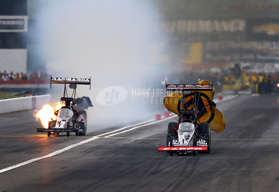 Sept. 2, 2013; Clermont, IN, USA: NHRA top fuel dragster driver Steve Torrence (right) races alongside Tommy Johnson Jr who has an engine fire during the US Nationals at Lucas Oil Raceway. Mandatory Credit: Mark J. Rebilas-