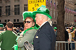 MARCH 17, 2011 - MANHATTAN: Couple, a gentleman and lady dressed in green hats, while watching St. Patrick's Day Parade 5th Avenue, directly across from St. Patrick's Cathedral entrance (not in view) with Saks 5th Avenue in background. Man's white hair pulled back in ponytail.