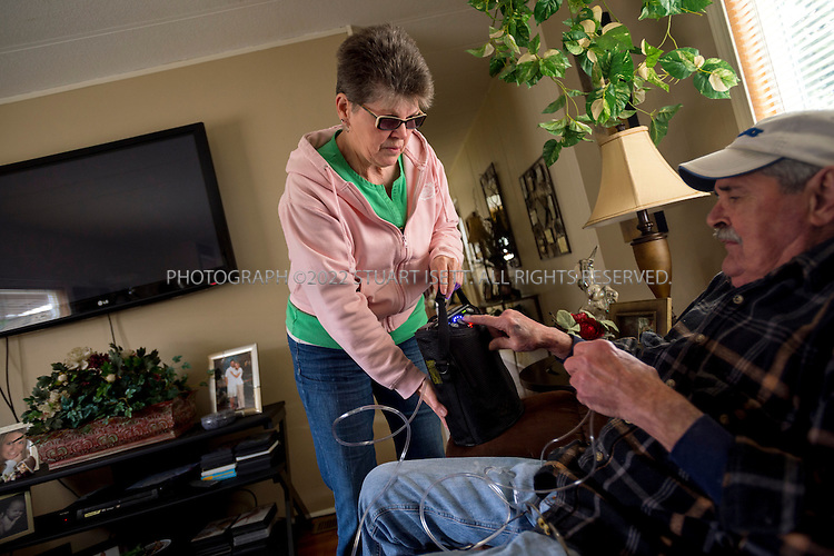 Arlington, WA - April 22, 2014: Linda Goff helps her husband, Ted Goff,&nbsp;73, with his oxygen supply in their home in Arlington Washington. A longtime smoker, he has stage 4 emphysema and was told by his doctors he has about six months to live (May is six months). He only has 24 percent oxygen in one lung and 8 percent in the other lung, not enough to be life-sustaining. <br /> &nbsp; &nbsp; <br /> About five years ago, the couple filled out an advanced directive at the suggestion of his doctor. But they didn't really understand any of the terms. When the pulmonologist gave Ted the prognosis last year, and asked whether Ted wanted to be on a ventilator, he suggested they see a video that would explain what that involved. After watching it, the Goffs realized they did not want him to be on a ventilator, or to be resusitated, or to receive any kind of intervention to sustain his life.<br /> <br /> (Photo by Stuart Isett for The Washington Post)