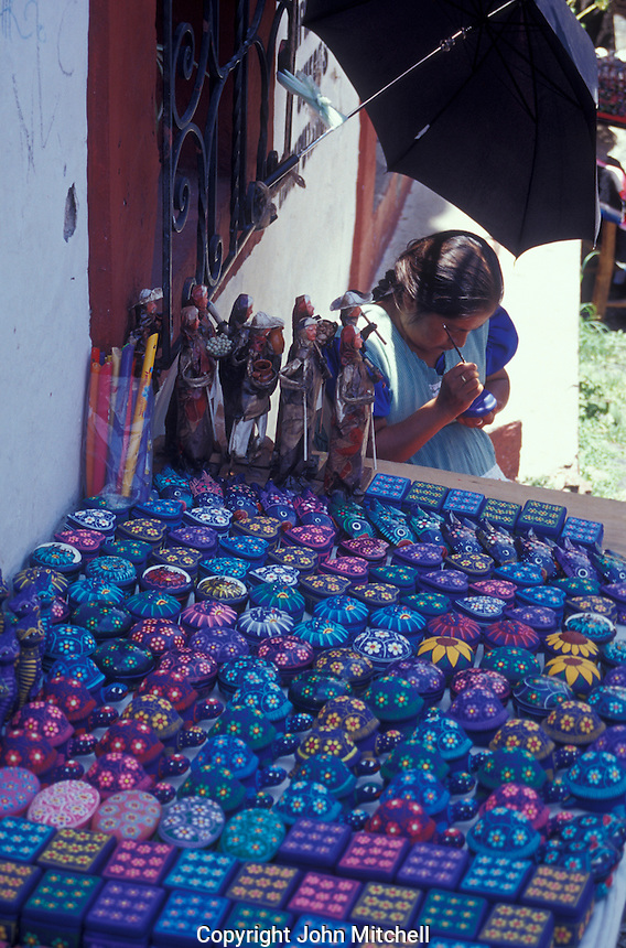 Indigenous woman painting a wooden box in the handicrafts market, Taxco, Mexico