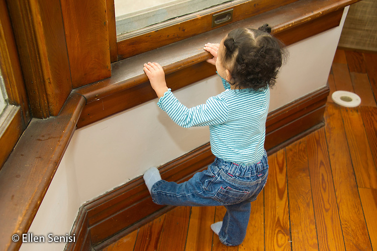 MR / Schenectady, NY. Toddler (1 year and 2 months old, African-American and Caucasian) in early walking stage practices standing on one foot while holding onto window sill for support. MR: Dal4. ID: AM-HD. © Ellen B. Senisi